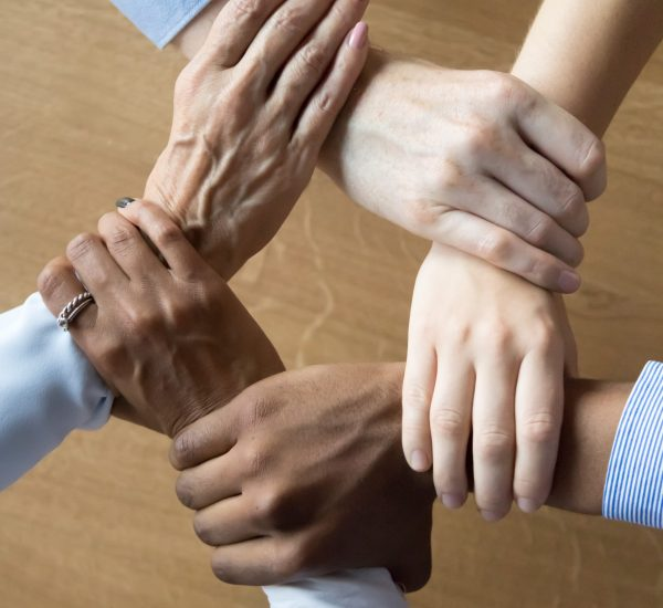 Close up multiracial business people holding each others wrists, join hands together, support and unity, team strength and power, colleagues involved in team building activity, vertical photo