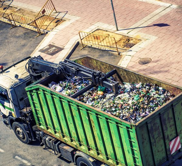top view of green truck collecting glass for recycling in the city