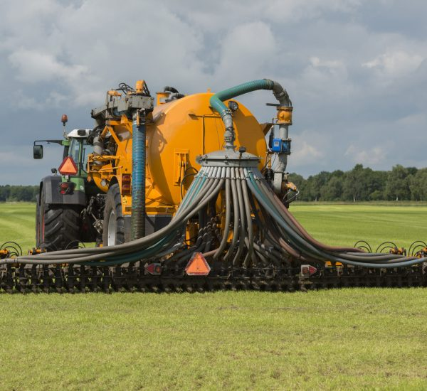 Agriculture, injecting of liquid manure with green tractor and yellow vulture spreader trailer.