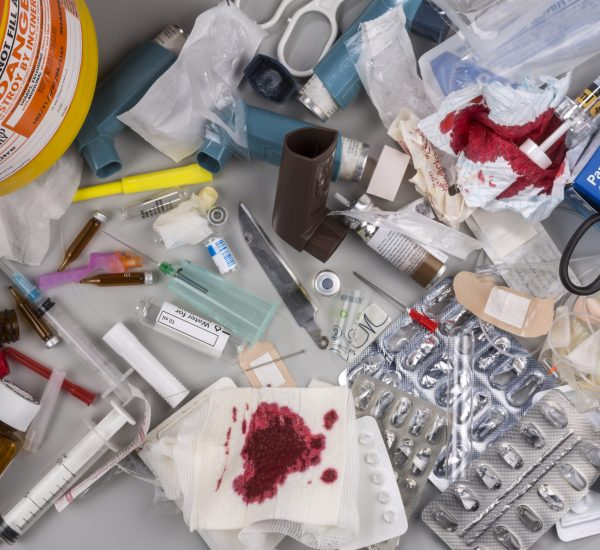 York, United Kingdom - August 10, 2015: Hazardous medical waste that needs to be carefully disposed of by incineration. Items include clinical waste such as used syringes and needles, used swabs, plasters and bandages. Used drug blister packs and ampules. Biomedical waste is potentially infectious.